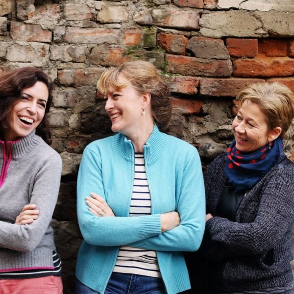 three smiling middle aged women standing by brick wall