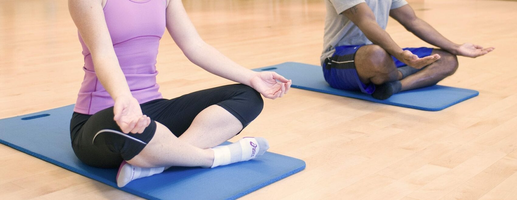 young man and woman in yoga class